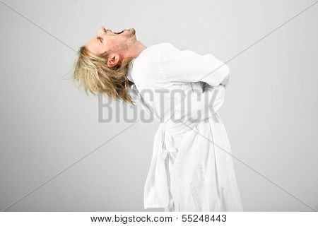 Mentally ill man in strait-jacket on gray background