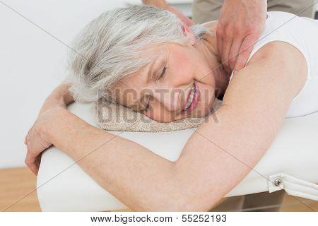 Männliche Physiotherapeuten massieren eine hochrangige Frau Schulter in der Arztpraxis