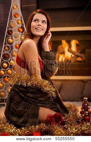 Portrait of hot girl smiling, posing in red bra and dressing gown surrounded with christmas decoration in front of cosy fireplace.