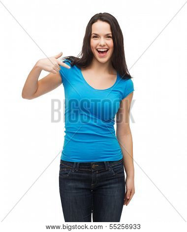 t-shirt design and gesture concept - smiling girl in blank blue t-shirt pointing her finger at herself