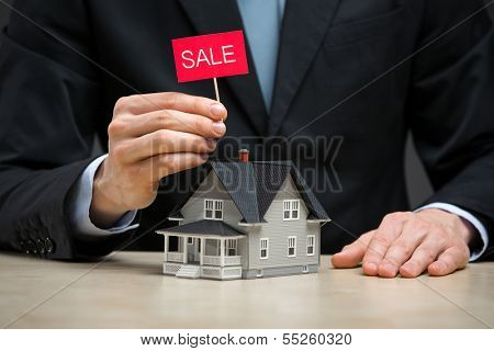 Close up of little home and hand keeping sale tablet. Concept of deal and real estate
