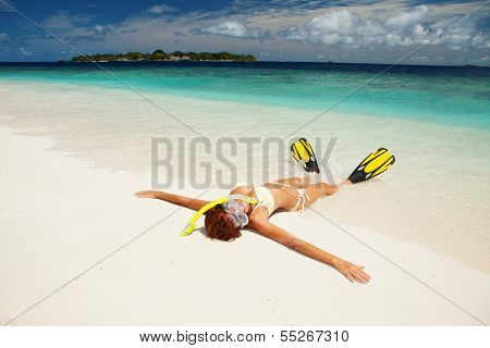 Cute woman with snorkeling equipment relaxing on the tropical beach