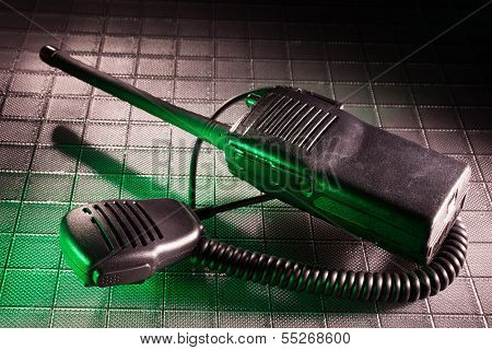 Green light spilling onto a two way radio and its microphone poster