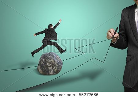Businessman Drawing Road With Arrow, Another Jumping Over Large Rock On The Way