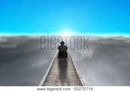 Businessman Sitting On Pier Looking Sunrise With Clouds, Blue Sky