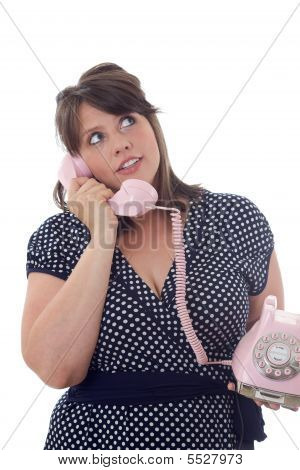 Woman Talking On A Pink Land-line Telephone; Isolated