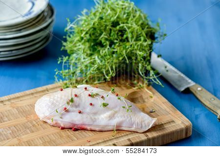 Raw Chicken Breast With The Skin Still On And Some Herbs In The Background And A Knife On A Blue Tab