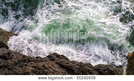 Waves From The Baltic Sea Splashing On Granite Cliffs With A Green Hue