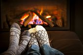 Feet in wool socks warming by cozy fire poster