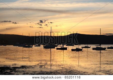 Yachts And Boats Moored On Tranquil Waters At Sunset