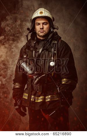 Firefighter with helmet and axe in a smoke