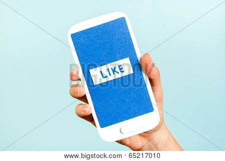 Like button on blue screen smartphone on blue background. Hand holding a smartphone with like button