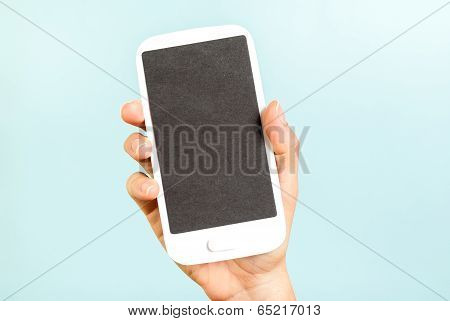 Hand holding black empty screen phone on blue background. Internet concept.