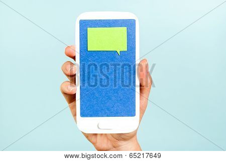 Hand showing a chat windows on smartphone on blue background. Internet concept.