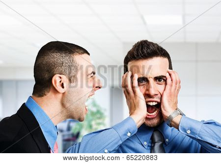 Angry businessman shouting to an employee