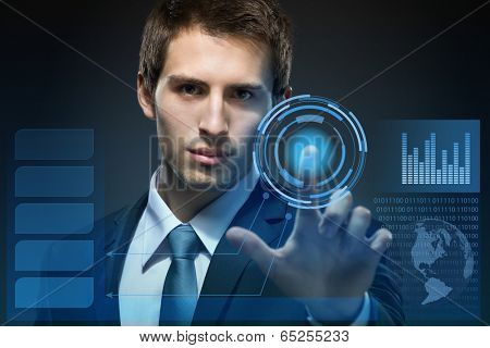 Businessman working with modern virtual technology pressing keys on touch screen on black background