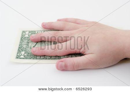 Child`s hand holding dollar.