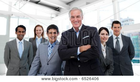 Senior Manager With Folded Arms Accompanied By His Team