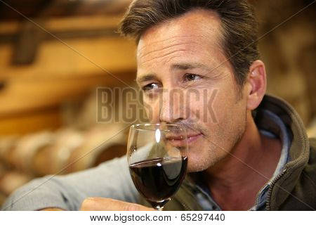 Winemaker tasting red wine in cellar
