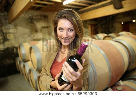 Woman in wine-cellar holding bottle of red wine