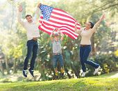 cheerful american family jumping with USA flag on 4th of july poster