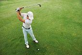 High overhead angle view of golfer hitting golf ball on fairway green grass poster