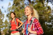 Active women - hiking girls walking in forest living healthy lifestyle doing outdoor activities. Female hikers trekking outside in woods wearing backpacks. Portrait of beautiful young blond hiker. poster