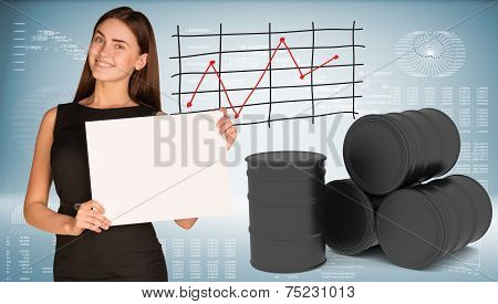 Businesswoman hold paper sheet. Black oil barrels are located next