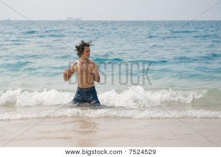 Man shaking his wet hair in the ocean.