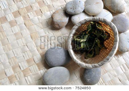 Basket of tea leaves on pebbles
