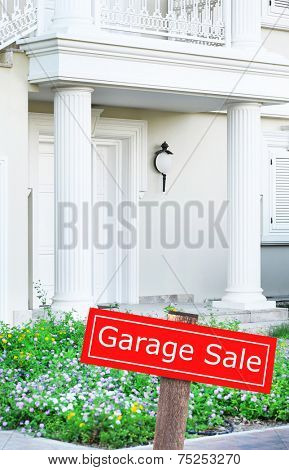 Garage sale sign in front of house