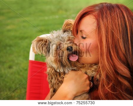 a woman with her beautiful dog cuddling outside at a park  poster