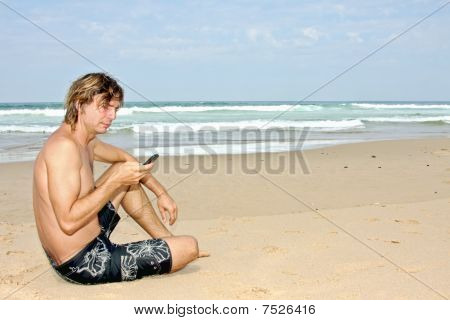 Young guy making a text message sitting on the beach