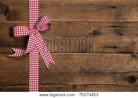 Wooden rustic background with a red white checked ribbon. Surface for a christmas present or gift certificate.