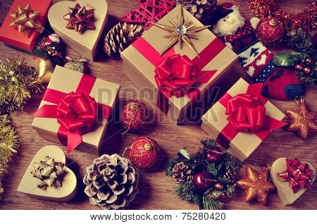 a pile of gifts and christmas ornaments, such as christmas balls, stars and tinsel, on a rustic wooden table