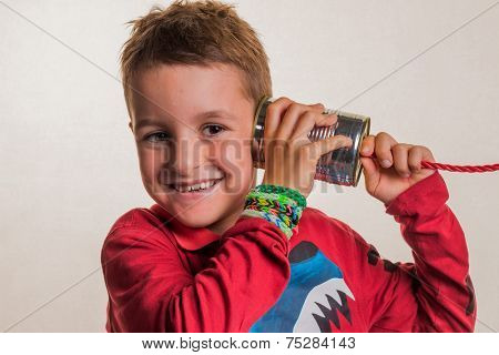 child listens in a tin can phone.