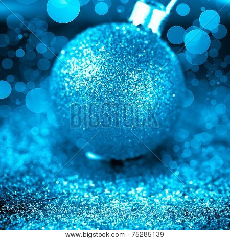 Christmas background with blue bauble on deep blue background with shiny sparkles and bokeh lights. Square composition. poster