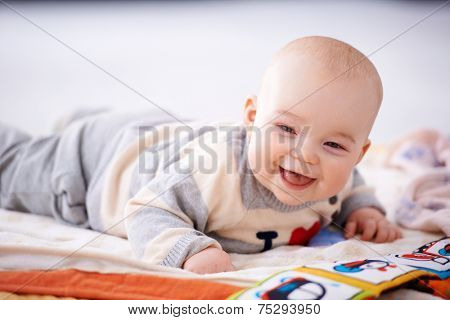 Happy gurgling baby lying on his bed playing with colorful pictures in a book looking at the camera with an adorable beaming smile of contentment poster