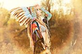 Close-up portrait of a beautiful girl wearing native american indian chief headdress. Western style. Jeans fashion. poster