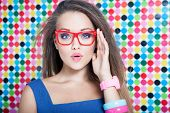Attractive surprised young woman wearing glasses on spotted background, beauty and fashion concept  poster