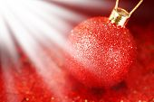 Christmas decoration with red shiny bauble over red background from glitter and sparkles in light rays poster