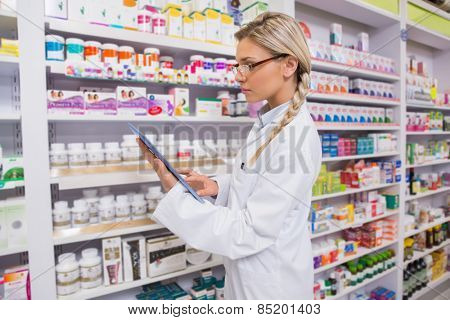Concentrated student using tablet pc in the pharmacy poster