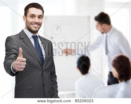 business, gesture and office concept - handsome buisnessman showing thumbs up in office
