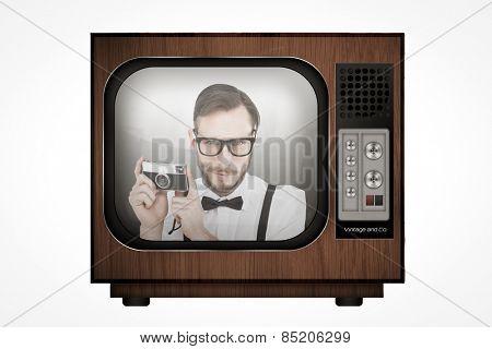 Geeky hipster holding a retro camera against retro tv