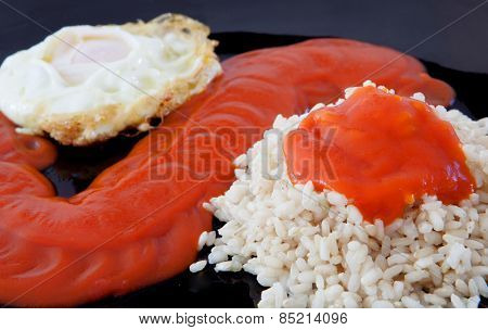 Fried egg with rice overcooked and tomato sauce
