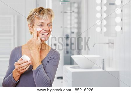 Old woman with skin care lotion standing in a bathroom (3D Rendering of background)