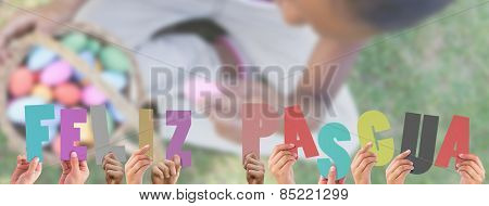 Hands holding up feliz pasqua against little girl sitting on grass counting easter eggs