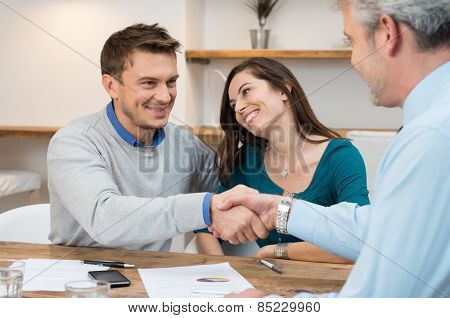 Happy young couple shaking hands for a financial agreement