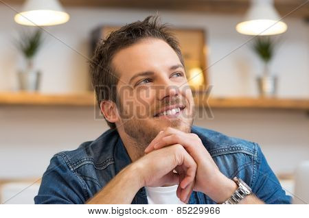 Closeup of smiling young businessman thinking in office