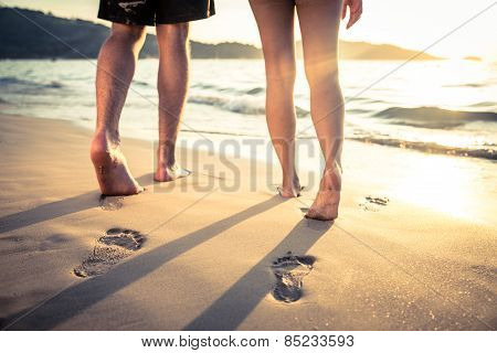 Couple of lovers walking on the each at sunset - Foot prints on the beach poster